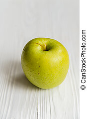 Single green apple on white wooden surface close