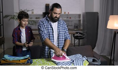 Single handsome father ironing clothes at home - Joyful...