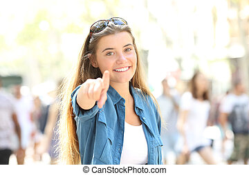 Single happy woman pointing at camera in the street