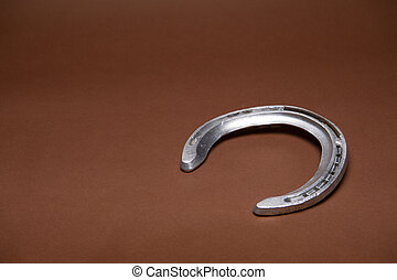 Single horseshoe isolated on a brown background