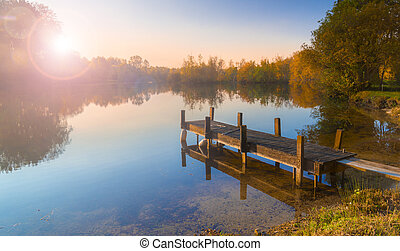 Single jetty on a calm lake - A wooden jetty juts out onto a...