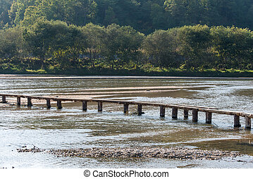 single lane log bridge over a shallow river in Museom ...