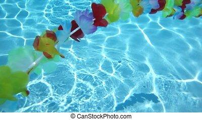 Single line Hawaiian flowers floating in pool water