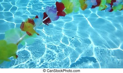 Single line Hawaiian flowers floating in pool water
