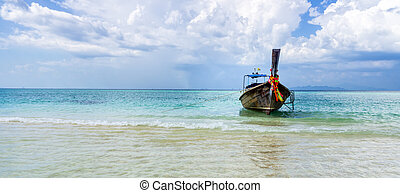 Single Long-tail boats on a shore of Bamboo Island, Thailand