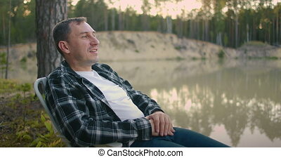 single man is relaxing at nature, sitting in armchair on ...
