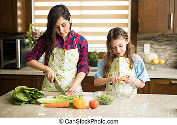 Portrait of a cute young single mother making a salad in the kitchen with her daughter