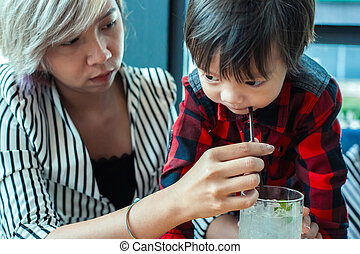 single mom help child drinking water from straw.