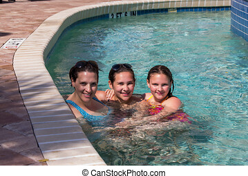 Single mom with two daughters in a resort pool lazy river. Family on vacation image.