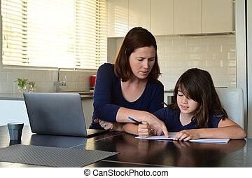 Single mother and daughter at home as the pandemic coronavirus (COVID-19) forces many employees and students to work and study from home. Real people. Copy space