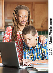 Single mother and her teen son work on computer