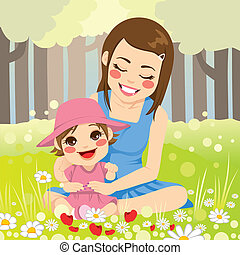 Beautiful single mother enjoying nature with her adorable little daughter on the park