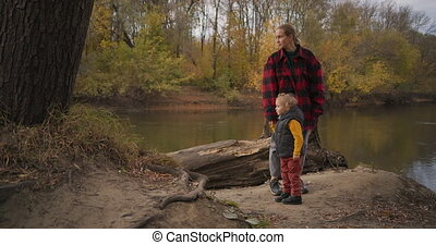 single mother is walking with little son at nature, resting ...