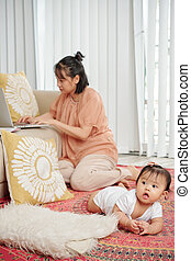 Single mother working on laptop - Young woman sitting on the...