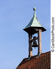 Single old church bell under canopy on roof