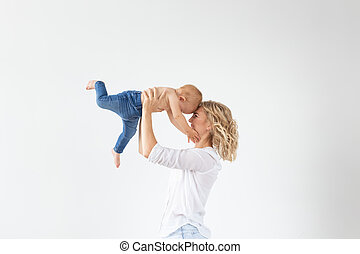 Single parent, motherhood and babyhood concept - Mother holding sweet baby girl on white background
