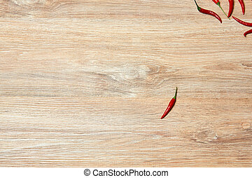 single pod of red chili pepper lies on a wooden surface away from a group of other fruits