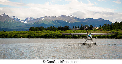 A bush plane performs taxi in in Alaska with Chugach Mountains in the Background