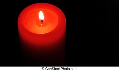 Single red candle in the dark.