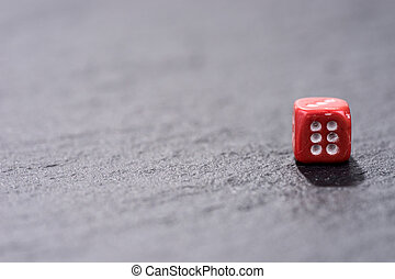 Single red dice on black background