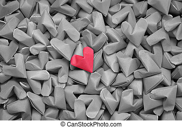 single red heart on many black and white hearts