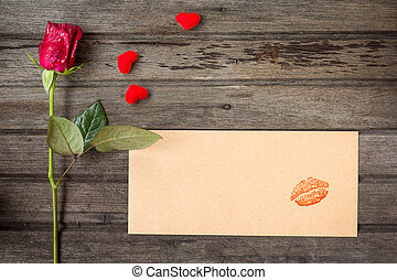 Single red rose with envelope with kiss and small hearts, on brown wooden background, top view, valentines day concept