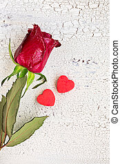 Single red rose with two small red cookies in shape of heart, on ols white wooden background, top view