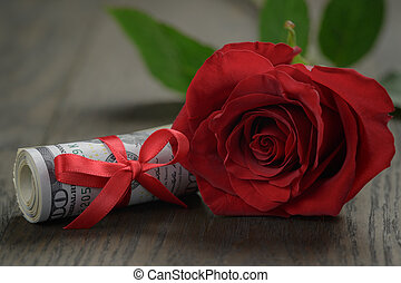 single red roses and bunch of dollars
