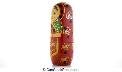 Single russian doll on white reflective background.