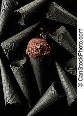Single scoop of chocolate ice cream amongst cones