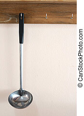 Single scoop with long handle hanging on wooden shelf.