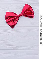 Single shiny red bow on white wood.