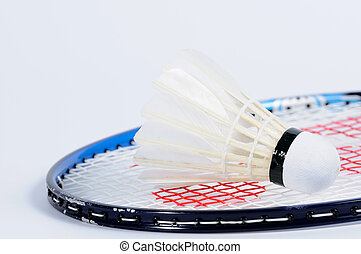 Single Shuttlecock lying on badminton racket.