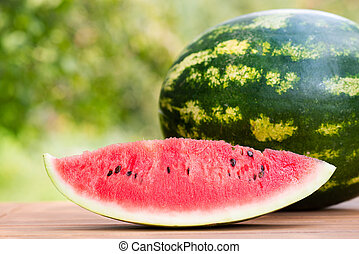 Single slice of ripe red juicy watermelon on a wooden table in the garden in summer time