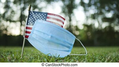Single small American, US or USA, flag with worn surgical face mask waving in the wind.. Concept showing Americas struggle with the pandemic.