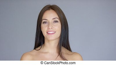 Single smiling woman over gray background - Single gorgeous...