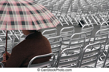 single spectator waits for the start of the show on aluminum cha