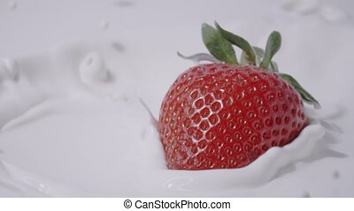 Single straberry falling into milk, slow motion shot on Red...