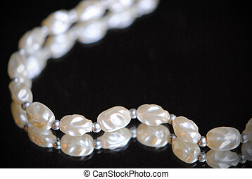 Single strand of freshwater pearls lying on a mirror.