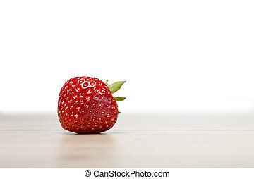 single strawberry on a table with white background
