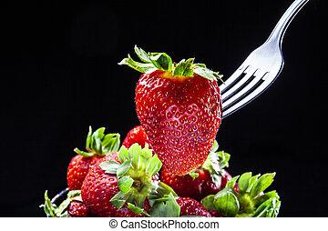 Single strawberry on fork