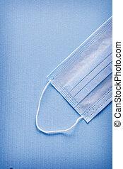 single surgical mask on blue background medical concept