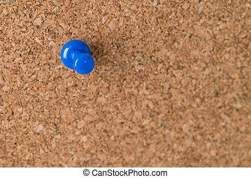 Single Thumb Tack on Cork Board - A single blue thumb tack...