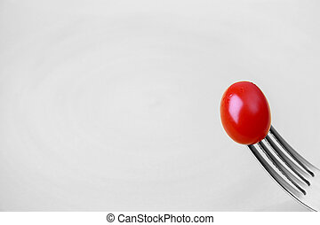 Single Tomato - Single tomato on a fork against a yellow...