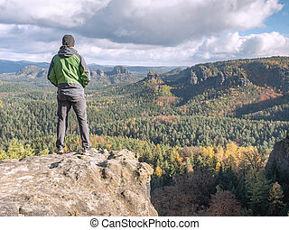 Single tourist on the edge of a mountain. Hilly landscape