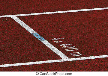 Closeup of a single red track lane, with 4x400m mark on the tarmack