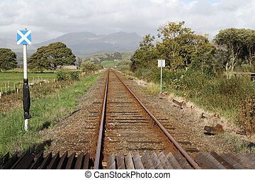 Single track rail-line with crossing and sign in a rural setting with trees, fields and mountains.