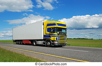 Single truck with blue-yellow cabin moving on highway.