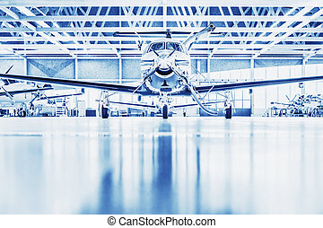 Single turboprop aircraft in big hangar. Focus on nose aircraft, colored on technical blue.