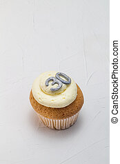 Single vanilla sponge cup cake with silver glitter number 30 on top of creamy white frosting isolated on rustic white background - celebration background